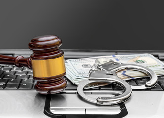 Gavel, handcuffs and money on the laptop keyboard. Close up.
