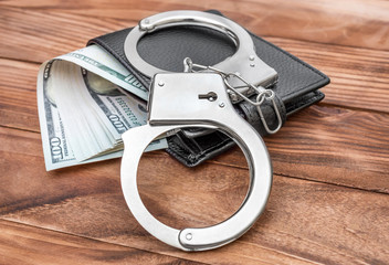 Handcuffs and wallet with money on the wooden table.