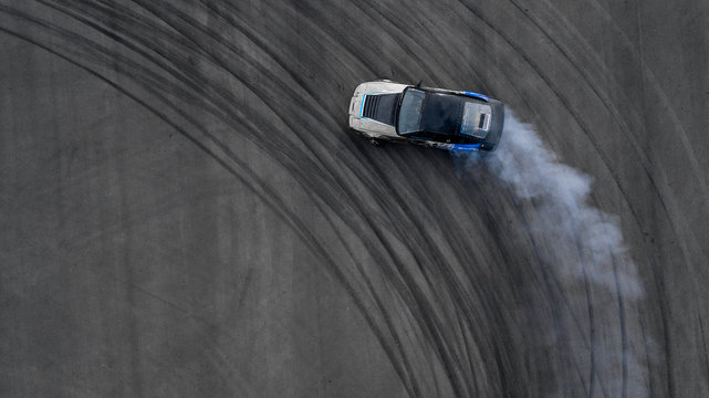 Aerial top view drifting car on asphalt road race track, Auto or automobile adrenaline active background concept.
