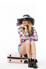Photo of blonde in hat with passport sitting on suitcase