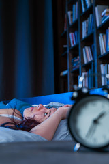 Image of unhappy woman with insomnia lying on bed next to alarm clock