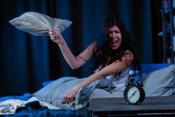 Picture of dissatisfied woman with insomnia throws pillow sitting on bed next to alarm clock