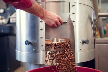 Picture of man's hand opening roaster with roasted coffee beans