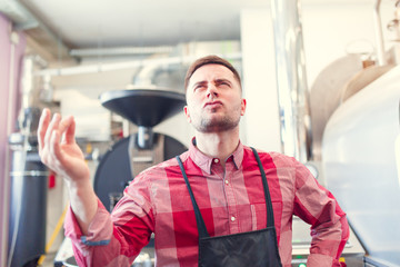 Image of happy barista man in apron on background of industrial coffee grinder