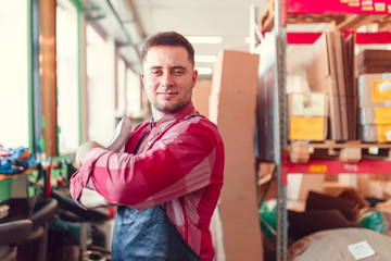 Portrait of man in apron with bag in hands at shop for making coffee