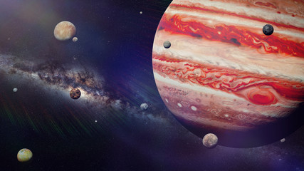 planet Jupiter with some of the 69 known moons lit by the Sun and the Milky Way galaxy
