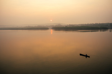 man in boat on the lake at sunset (dawn)
