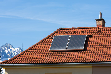 green energy, solar collectors on the roof of a family house