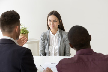 Confident female applicant smiling at job interview with diverse hr managers, young happy professional candidate talks to multiracial recruiters makes good first impression, employment hiring concept