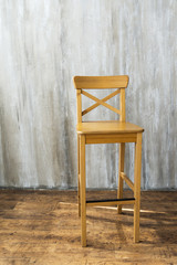 Wooden high stool on grey background.