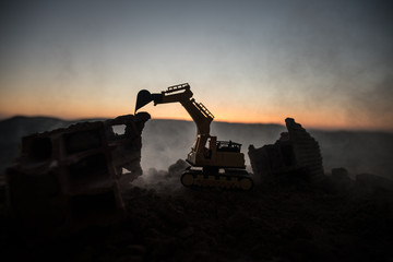 Construction site on a city street. A yellow digger excavator parked during the night on a construction site. Industrial concept table decoration on dark foggy toned background