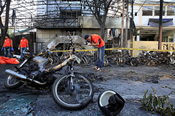 Forensic police officer takes pictures of debris near burned motorcycles following a blast in Surabaya