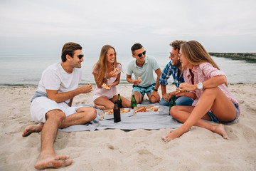 Group of young smiling guys and girls resting together on the beach, sitting near the sea while eating pizza with drink. Dressed in casual clothes.