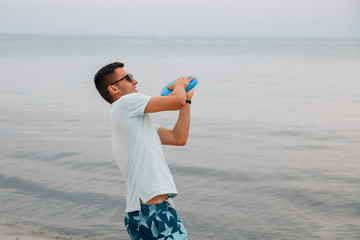 Cheerful guy about to throw a frisbee disk, playing near the sea.