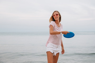 Young charming woman playing frisbee near the sea, holding frisbee disk. Dressed in shorts and t-shirt, in sunglasses.