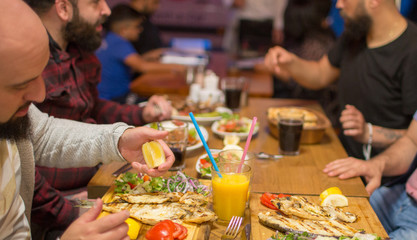 Group of people in restaurant enjoying Middle Eastern food. Selective focus