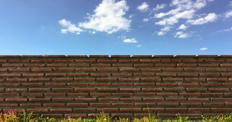 brick wall with white clouds in blue sky. blue skies over red brick wall. shrubs and brick fence on blue sky background.
