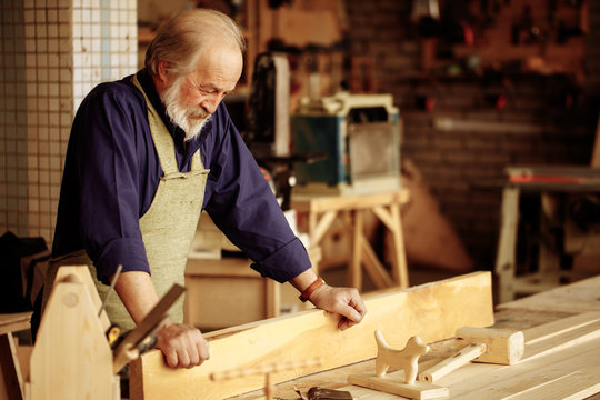cheerful old handyman wearing shirt and apron is looking at the prepared wooden dog in the garage