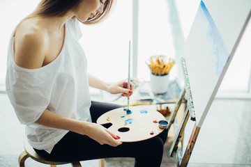 Caucasian woman painter with palette on her kneels , dipping paintbrush into oil colours drawing a painting with blue watercolor.