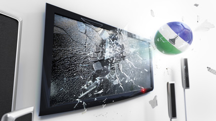 Soccer ball with the flag of Lesotho kicked through a shattering tv screen.(3D rendering series)