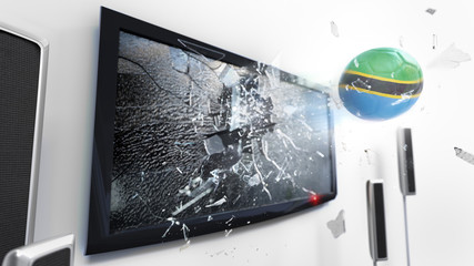 Soccer ball with the flag of Tanzania kicked through a shattering tv screen.(3D rendering series)