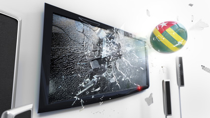 Soccer ball with the flag of Togo kicked through a shattering tv screen.(3D rendering series)