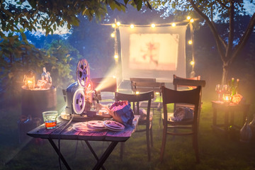 Cinema with old analog films in summer garden the evening