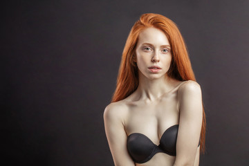 6d63a45a01e5c Slim young girl with long gorgeous red hair and strapless bra on black  background with copyspace