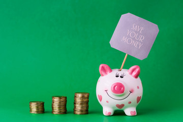 Piggy bank and towers coins. The inscription Save your money. Copy space.