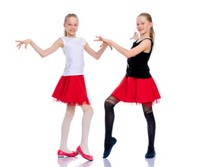 Two cheerful little girls are dancing.