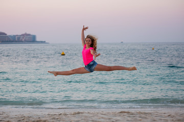 Cute young girl doing split-jump at the beach