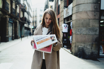 Young caucasian female stunned with the latest news she read in a morning newspaper amidst the street . Business woman in trendy clothes reading market news while going to the office.