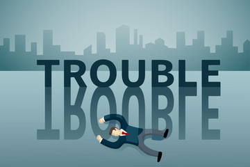 business man lie down on the floor in front of TROUBLE word.