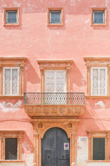 Gallipoli, Apulia - A pink facade with a barn door and several windows
