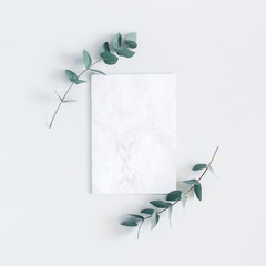 Marble paper blank, eucalyptus branches on pastel gray background. Flat lay, top view, square, copy...