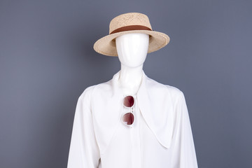 Hat, white blouse and sunglasses. Female mannequin with white chiffon shirt, straw hat and sunglasses, grey background. Ladies stylish look.