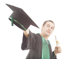 young man throwing graduation cap in the air