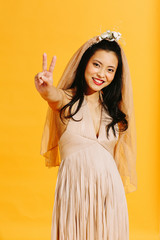 Portrait of a happy smiling bride holding her hand up in the shape of a v sign, isolated on yellow studio background