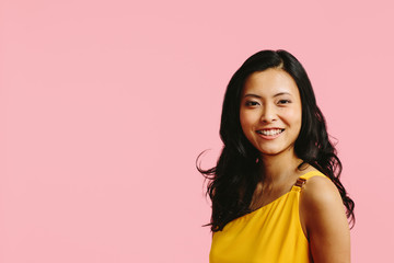 Portrait of a young, smiling asian woman, isolated on pink studio background