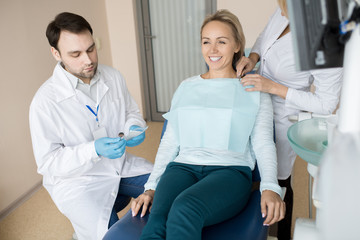 Crop assistant preparing cheerful girl while dentist getting special clean tools from bag.