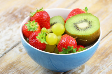 Bowl full of fresh fruit: strawberries, kiwi and grapes