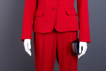 Close up mannequin with female suit and wallet. Women red blazer and trousers, cropped image. Feminine brand apparel.