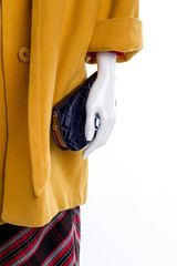 Female mannequin with coat and wallet close up. Yellow cashmere overcoat, purse and skirt, cropped image. Feminine casual apparel.
