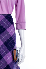 Female mannequin in purple apparel. Women blouse, skirt and wallet, copy space. Boutique of feminine attire and accessories.