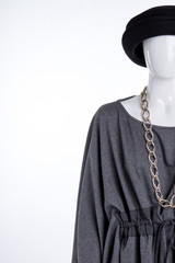 Black hat, grey blouse and jewelry. Female mannequin dressed in modern garment, copy space. Ladies stylish look.