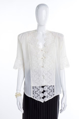 White lace blouse for women. Female mannequin clothed in satin shirt and black skirt. Feminine elegance and style.