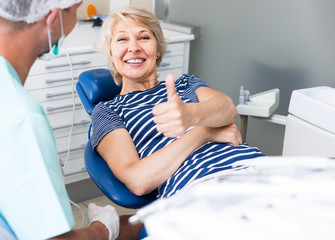 Portrait of smiling satisfied woman visiting dentist giving thumbs up