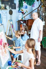 Full length portrait of mature art teacher watching group of children painting in art class