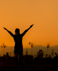 Silhouette happy woman standing on a sunset