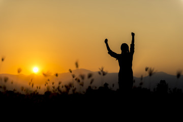 Silhouette woman at sunset standing elated with arms raised up above her head.